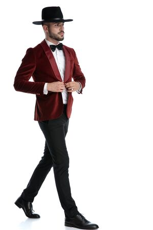 confident young man in red velvet tuxedo walking and looking to side, fixing coat, isolated on white background, full body