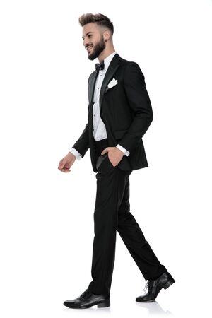 vista laterale di uno splendido uomo d'affari che indossa uno smoking nero che cammina con una mano in tasca sulla sua strada felice su sfondo bianco studio