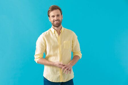 Positive casual man holding his hands together and smiling, standing on blue studio background