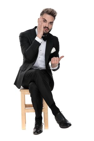 gorgeous businessman wearing black tuxedo sitting on a wooden chair with legs crossed and touching his face while pointing aside worried on white studio background Фото со стока
