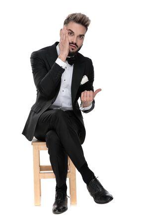 Wunderschöner Geschäftsmann mit schwarzem Smoking, der mit gekreuzten Beinen auf einem Holzstuhl sitzt und sein Gesicht berührt, während er besorgt auf weißem Studiohintergrund zur Seite zeigt Standard-Bild