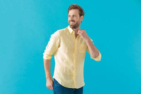 Cheerful casual man laughing and adjusting his collar, holding his hand in his back pocket and looking away, standing on blue studio background