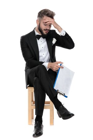 gorgeous businessman wearing black tuxedo sitting with legs crossed on a wooden chair and holding a clipboard while slapping his forehead on white studio background 版權商用圖片