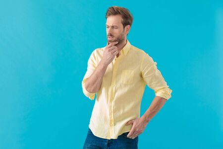 Pensive casual man holding his hand on his chin and in his pocket, solving his problems and thinking, standing on blue studio background