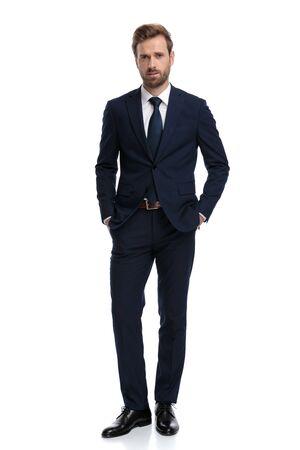 Junger Geschäftsmann im dunkelblauen Anzug, der die Hände in den Taschen hält und isoliert auf weißem Hintergrund steht, Ganzkörper Standard-Bild