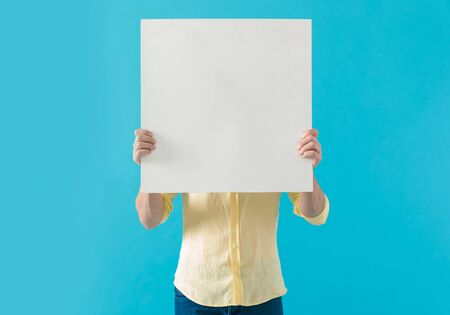 Young casual man hiding his face behind a blank billboard, standing on blue studio background