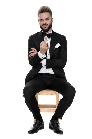 businessman wearing black tuxedo sitting on a wooden chair and making a you sign being grumpy on white studio background