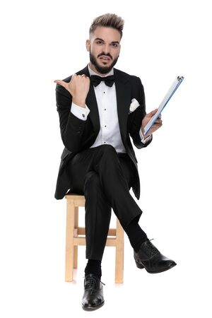 young businessman wearing black tuxedo sitting on a wooden chair with legs crossed holding his clipboard and pointing aside disgusted on white studio background Banque d'images
