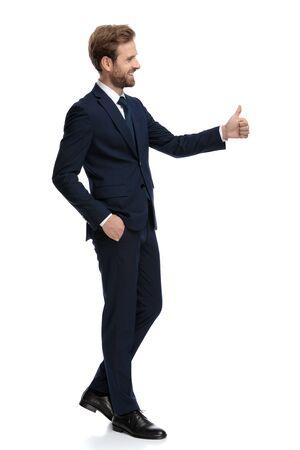 vista laterale dell'uomo d'affari felice che sorride e che fa il segno del pollice in alto, camminando isolato su sfondo bianco, corpo pieno Archivio Fotografico