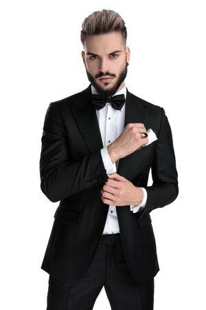 Encantador empresario vistiendo esmoquin negro de pie y fijando la manga mientras mira a la cámara fresca sobre fondo blanco de estudio