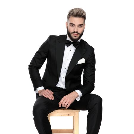 good looking businessman wearing black tuxedo sitting relaxed and resting his hands on his lap while looking at camera serious on white studio background