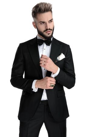 good looking businessman wearing black tuxedo standing and fixing sleeve while looking aside cool on white studio background