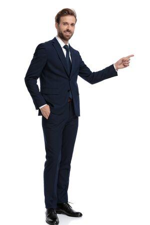 Joven empresario en traje azul marino apuntando con el dedo a un lado y sonriendo, de pie aislado sobre fondo blanco, de cuerpo completo
