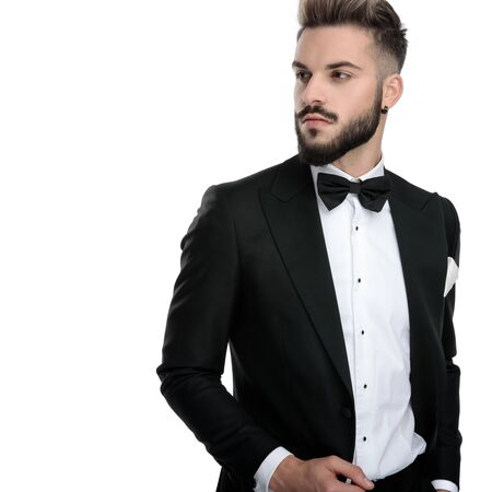attractive businessman wearing black tuxedo standing with one hand in pocket and looking aside with class on white studio background