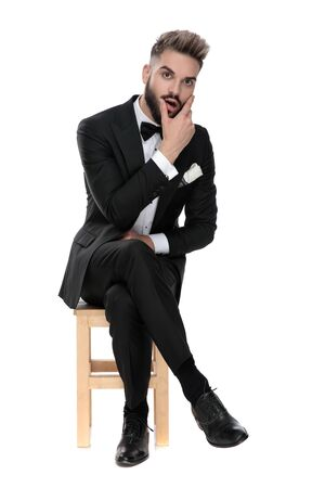 handsome businessman wearing black tuxedo sitting on a wooden chair with legs crossed and rubbing his face shocked on white studio background
