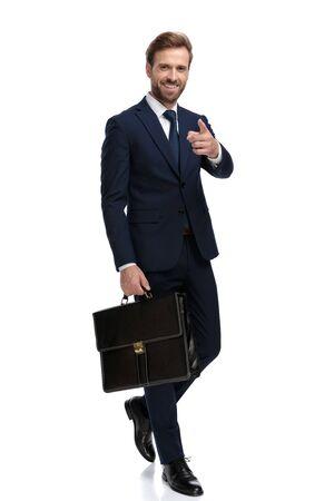 homme d'affaires heureux tenant une valise et un doigt pointé, marchant isolé sur fond blanc, corps entier Banque d'images