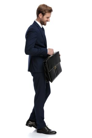 happy businessman in navy blue suit holding suitcase and smiling, walking isolated on white background, full body 版權商用圖片
