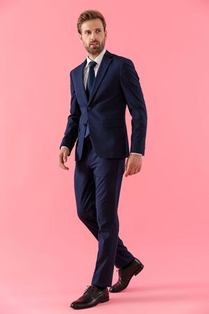 Pensive businessman curiously looking away while walking on pink studio background Banco de Imagens
