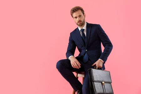 Upset businessman holding a briefcase and looking forward while sitting on a stool on pink studio background