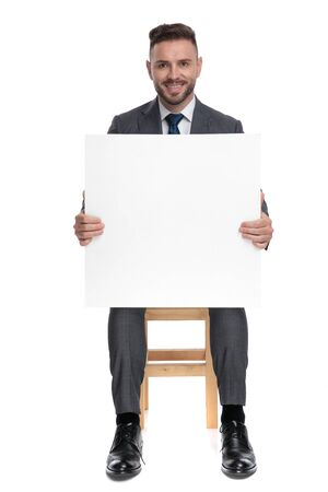 smiling fashion model holding empty board and sitting isolated on white background, full body