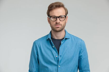 young casual model wearing glasses and frowning on grey background, portrait
