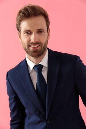 Close up of a cheerful businessman smiling while standing on pink studio background