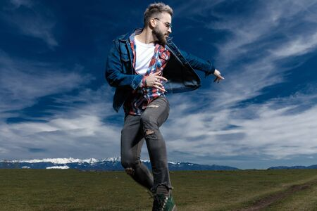 Handsome young man running and escaping while wearing jeans jacket and sunglasses, moving on outdoor nature background