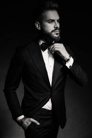 young businessman wearing tuxedo standing with one hand in pocket while fixing his bowtie with style on black studio background