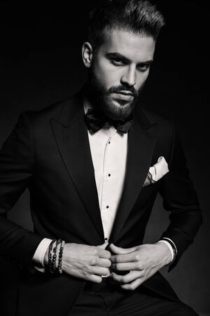 handsome businessman wearing tuxedo sitting and fixing his jacket while posing with attitude on black studio background Standard-Bild