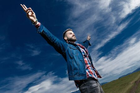 Handsome man gesturing peace with his arms wide open while wearing jeans jacket and standing on outdoor nature background Archivio Fotografico