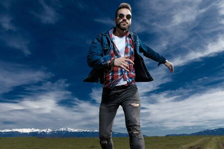 Brave fashion model jumping while wearing jeans jacket and sunglasses, stepping on outdoor nature background