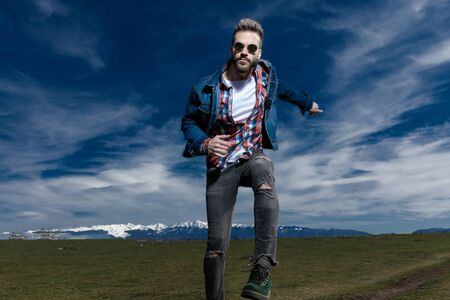 Young man jumping while wearing jeans jacket and sunglasses, moving on outdoor nature background