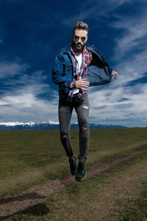 Confident young man running and jumping while wearing jeans jacket and sunglasses, moving on outdoor nature background Stock Photo