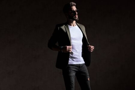 cool fashion guy adjusting coat and looking to side in a fashion light in studio on brown background