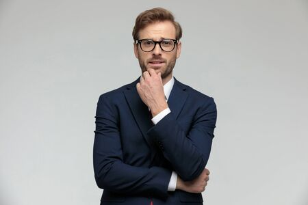 young businessman wearing suit and eyeglasses standing and pondering a decision pensive on gray studio background