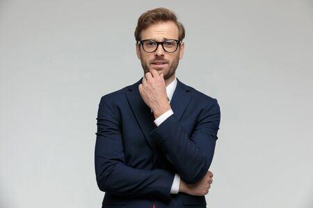 Joven empresario vistiendo traje y anteojos de pie y reflexionando sobre una decisión pensativa sobre fondo gris de estudio