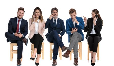 Team of 5 businessmen talking, reading and writing on their phones while waiting for a job interview sitting on chairs on white studio background