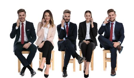 Team of 5 young businessmen talking on phone while sitting on chairs on white studio background Banco de Imagens
