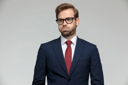 sexy businessman wearing suit and eyeglasses standing and puffing cheeks anxious on gray studio background