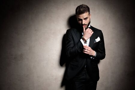 elegant man in tuxedo looking to side and touching lips in a fashion pose on brown background in studio Foto de archivo