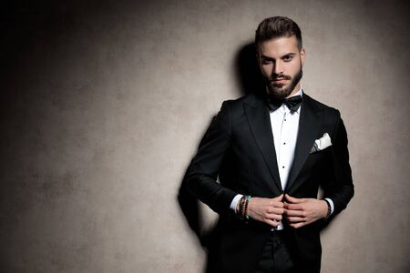 young elegant model in tuxedo adjusting coat in a fashion light on brown background in studio