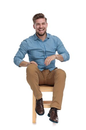 happy casual man wearing denim shirt, holding hands on knee and laughing, sitting isolated on white background, full body