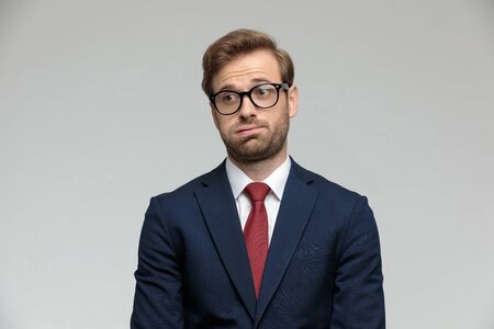 sexy businessman wearing suit and eyeglasses standing and holding air in his mouth anxious on gray studio background