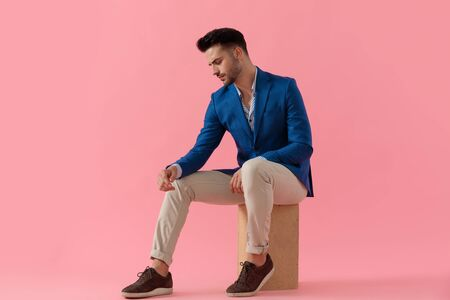 young smart casual man looking down side and holding elbow on knee in a fashion pose on pink background, full length