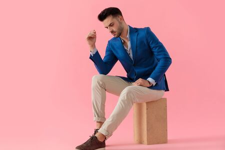 sexy cool smart casual guy looking down and holding elbow on knee in a fashion pose on pink background, full length 스톡 콘텐츠