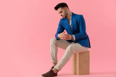 sexy young smart casual man sitting on a wooden box and looking down in a fashion pose on pink background, full body
