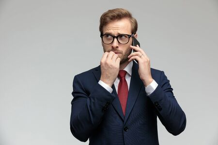 handsome businessman wearing suit and eyeglasses standing and talking on the phone while biting his fingernails anxious on gray studio background