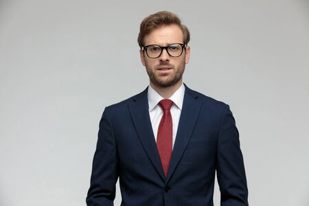 handsome businessman wearing suit and eyeglasses standing and looking at camera fearful on gray studio background Reklamní fotografie