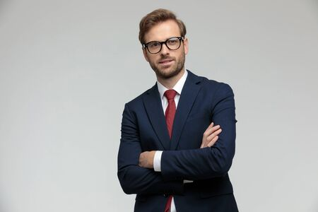 handsome businessman wearing suit and eyeglasses standing with arms crossed and looking ahead satisfied on gray studio background