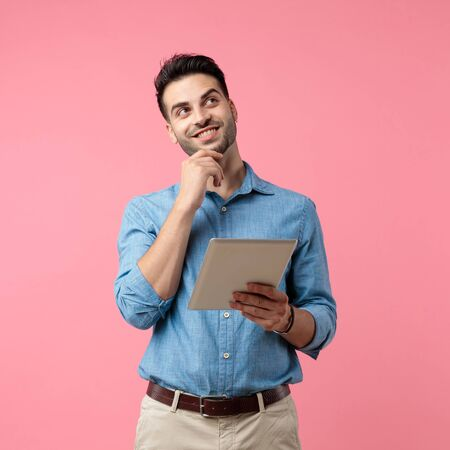 young casual man holding tab and holding hand to chin, thinking and looking up, standing on pink background Banque d'images